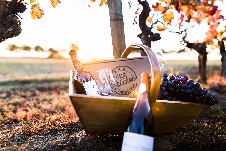 panier avec des bouteilles de vin sur une petite table - Photo pour le site ptit bouchon, vente de vin en ligne
